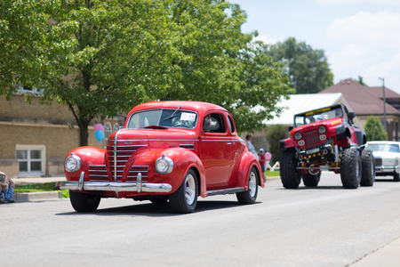 Kokomo, Indiana, USA - June 30, 2018: Haynes Apperson Parade, A Plymouth Classic Car color red going down the street during the parade