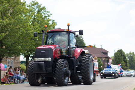Kokomo, Indiana, USA - June 30, 2018: Haynes Apperson Parade, A large red tractor Case IH Magnum pulling a wagon going down the road Editorial