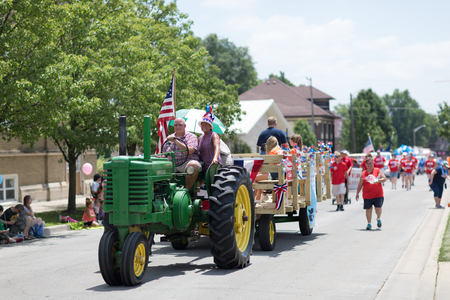 Kokomo, Indiana, USA - June 30, 2018: Haynes Apperson Parade, Old John Deere classic tractor color green , pulling a wagon down the road and carrying the american flag Editorial