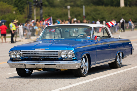Chicago, Illinois, USA - June 16, 2018: The Puerto Rican Day Parade, Puerto RIcan driving a Chevrolet Bel Air blue Classic car with puerto rican flags during the parade