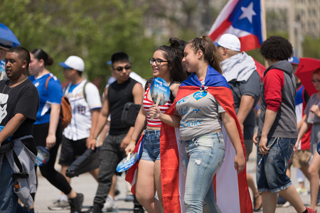 Chicago, Illinois, USA - June 16, 2018: The Puerto Rican Day Parade, puerto rican people celebrating waving puerto rican flags during the parade Editorial