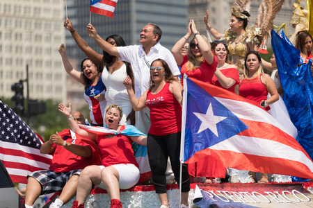 Chicago, Illinois, USA - June 16, 2018: The Puerto Rican Day Parade, Puerto Rican people on top of a float celebrating waving puerto rican flags during the parade Editorial