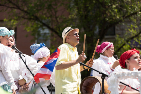 Chicago, Illinois, USA - June 16, 2018: The Puerto Rican Peoples Parade, puerto rican people with traditional clothing, singing and playing bomba music with barril de bomba