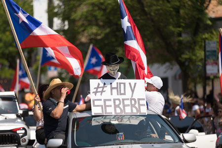 Chicago, Illinois, USA - June 16, 2018: The Puerto Rican Peoples Parade, Puerton rican people riding on cars celebrating with puerto rican flags and a sign that says Hoy Se Bebe