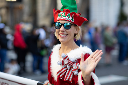 New Orleans, Louisiana USA - November 24, 2018: The Bayou Classic Parade, Woman wearing Christmas outfit promoting Nola Christmas Fest