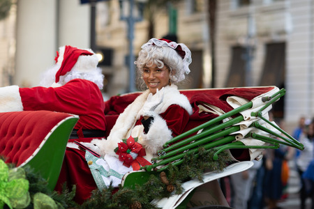 New Orleans, Louisiana USA - November 24, 2018: The Bayou Classic Parade, African American woman riding on a carriage next to Santa Claus,  dress up as Mrs. Claus Archivio Fotografico - 116933442