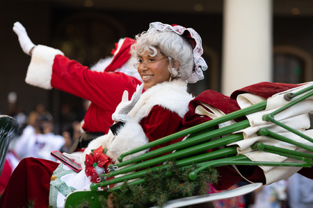 New Orleans, Louisiana USA - November 24, 2018: The Bayou Classic Parade, African American woman riding on a carriage next to Santa Claus,  dress up as Mrs. Claus