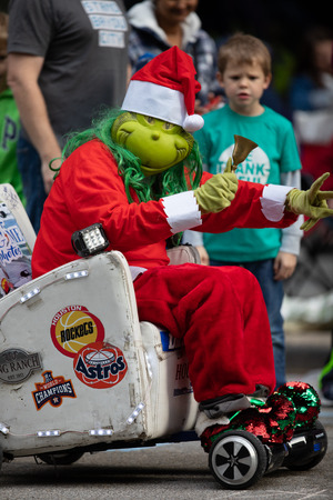 Houston, Texas, USA - November 22, 2018 The H-E-B Thanksgiving Day Parade, Person dress up as the grinch with a hand bell on a motorized sofa
