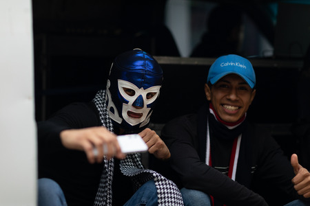 Matamoros, Tamaulipas, Mexico - November 20, 2018: The November 20 Parade, Two young men, one wearing a luchador mask pose for the camera while holding a phone