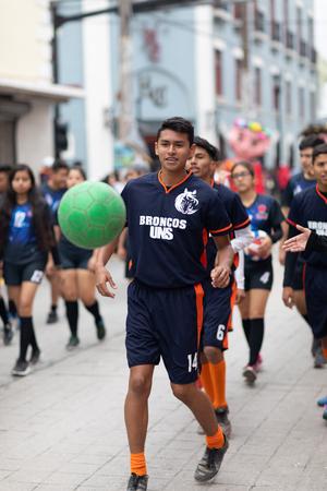 Matamoros, Tamaulipas, Mexico - November 20, 2018: The November 20 Parade, Young men playing Soccer with a green ball during the parade