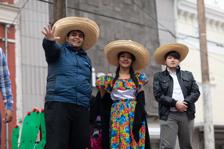 Matamoros, Tamaulipas, Mexico - November 20, 2018: The November 20 Parade, Woman and men with sombreros and traditional mexican clothing going down the road on a float