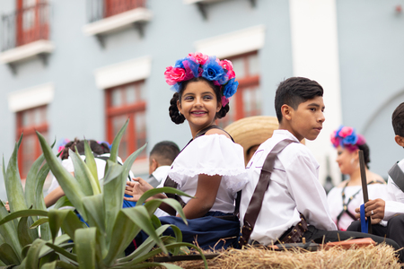 Matamoros, Tamaulipas, Mexico - November 20, 2018: The November 20 Parade, Young girl and boy wearing traditional mexican clothing going down the street on a float
