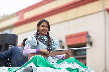 Matamoros, Tamaulipas, Mexico - November 20, 2018: The November 20 Parade, Young Girl wearing traditional clothing Holding a toy rifle at the parade Editorial