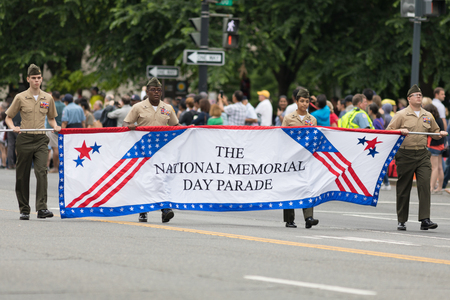 Washington, D.C., USA - May 28, 2018: The National Memorial Day Parade, Men and woman wearing service charlie uniforms carry the National Memorial day Parade Banner