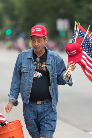 Man on the streets of washington DC, selling flags and hats with the words, Make America Great Again