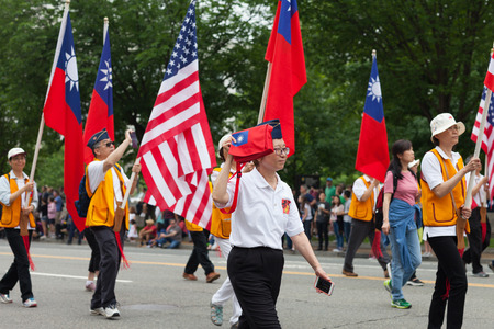 Washington, D.C., USA - May 28, 2018: The National Memorial Day Parade, Taiwan military veterans carrying the american and taiwanese flags down constitution avenue