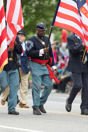 Washington, D.C., USA - May 28, 2018: The National Memorial Day Parade, African american Men dress up as civil war union soldiers, carrying the american flag, walking down constitution avenue
