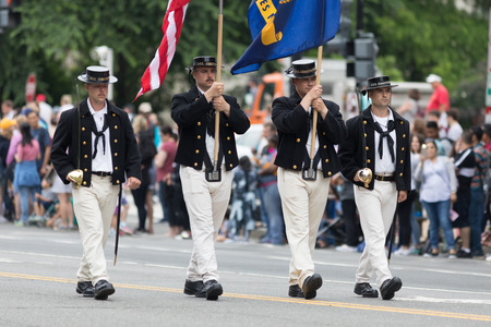 Washington, D.C., USA - May 28, 2018: The National Memorial Day Parade, Men dress up as crew members of the U.S.S. Constitution, carrying the american flag down constitution evenue