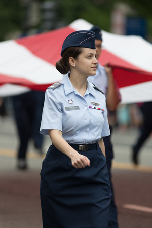 Washington, D.C., USA - May 28, 2018: The National Memorial Day Parade, Members of the United States Air Force carry a giant american flag, marching down Constitution Avenue,