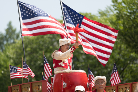 Washington, D.C., USA - July 4, 2018, The National Independence Day Parade, Chinese, wearing traditional clothing, playing drums, and with american flags, going down constitution avenue during the parade