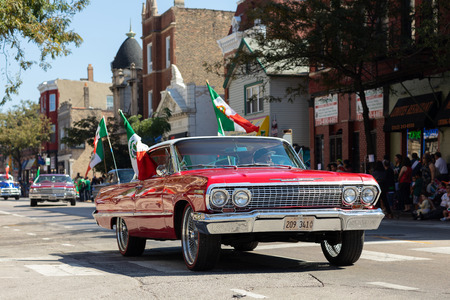Chicago, Illinois, USA - September 15, 2018: Pilsen Mexican Independence Day Parade, Chevrolet, impala carrying the mexican flag, going down the street