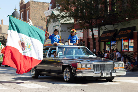 Chicago, Illinois, USA - September 15, 2018: Pilsen Mexican Independence Day Parade, Cadillac, with children on top, waving a large mexican flag