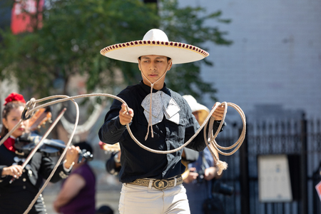 Chicago, Illinois, USA - September 15, 2018: Pilsen Mexican Independence Day Parade, Man wearing traditional charro clothing, handling a lasso