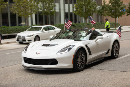 Houston, Texas, USA - November 11, 2018: The American Heroes Parade, Chevrolet Corvettes, with american flags, transporting military veterans down the street during the parade