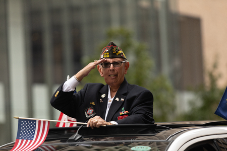 Houston, Texas, USA - November 11, 2018: The American Heroes Parade, Military veteran saluting with the american flag, scars on his face Editorial