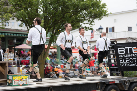 Frankenmuth, Michigan, USA - June 10, 2018 Men and women playing traditional german music drinking beer dancing and wearing traditional german clothing at the Bavarian Festival Parade.
