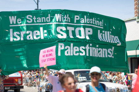 Chicago, Illinois, USA - June 24, 2018: the LGBTQ Pride Parade, People protesting, carrying a banner that says We Stand with Palestine! Israel: Stop Killing Palestinians!