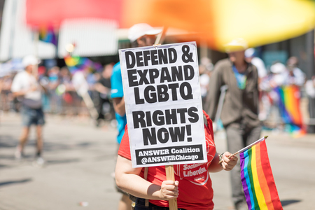 Chicago, Illinois, USA - June 24, 2018: the LGBTQ Pride Parade, Woman holding a sign that says, Defend and expand LGBTQ rights now!