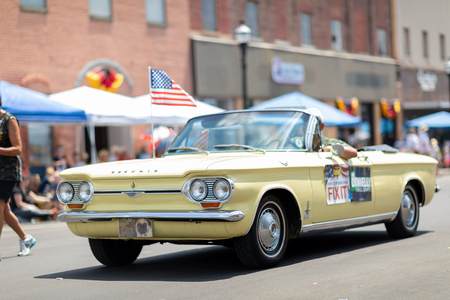 Jasper, Indiana, USA - August 5, 2018: The Strassenfest Parade, Man driving a Chevrolet, Corvair, classic car with the american flag 写真素材 - 117154090