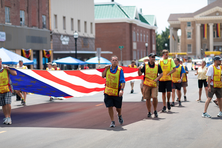 Jasper, Indiana, USA - August 5, 2018: The Strassenfest Parade, Men from the Knights of Columbus, promoting help for people with Disabilities, carrying a giant american flag