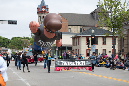 Stoughton, Wisconsin, USA - May 20, 2018: Annual Norwegian Parade, Women carrying a banner that says Metal Mom, with a large balloon in shape of a woman in the background