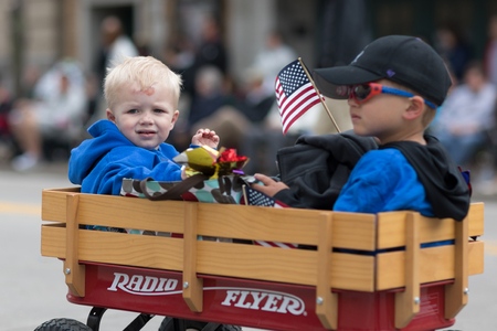 Stoughton, Wisconsin, USA - May 20, 2018: Annual Norwegian Parade, Children riding on a Radio Flyer, wagon, with american flags, during the parade 報道画像