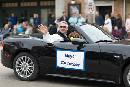 Stoughton, Wisconsin, USA - May 20, 2018: Annual Norwegian Parade, Mayor Tim Swadley waves at the camera as he passes by in a car