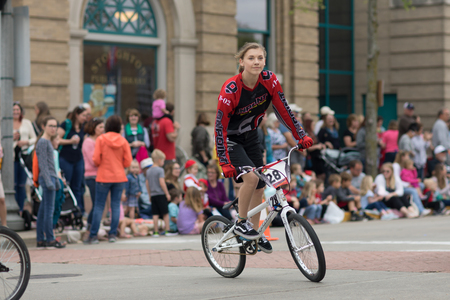 Stoughton, Wisconsin, USA - May 19, 2018: Syttende Mai Youth Parade, Girl riding mountain bicycles, with protective gear, during the parade Redakční