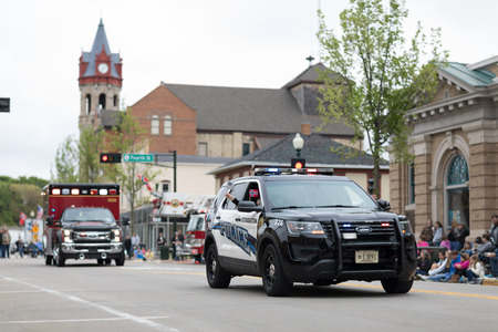 Stoughton, Wisconsin, USA - May 20, 2018: Annual Norwegian Parade, A Police car leads the parade down the road, with the american and norwegian flags