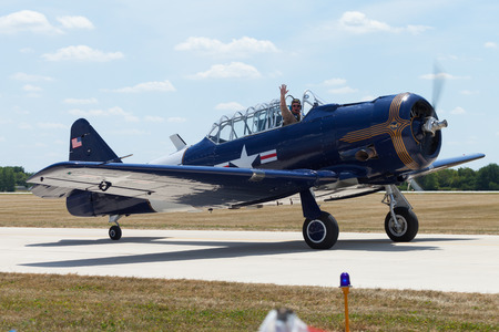 Indianapolis, Indiana, USA - June 23, 2012: Indianapolis Airshow, T-6 Texan taxing after landing, pilot waving at spectators Editorial