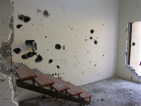Wall with bullet holes from 50 cal machinegun, assualt rifles, and grenades Imagens