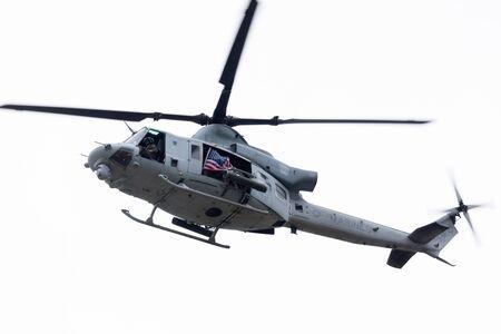 Louisville, Kentucky, USA - 13. April 2019: Donner über Louisville, United States Marine Corps uh-1 mit einer amerikanischen Flagge, die über den Ohio River fliegt?