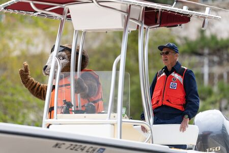 Wilmington, North Carolina, USA - April 6, 2019: The North CarolinaAzalea Festival, Members of the U.S. Coast Guard, Auxiliary, on a boat going down 3rd street
