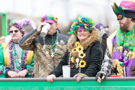 St. Louis, Missouri, USA - March 2, 2019: Bud Light Grand Parade, woman wearing a colorful feather hat looking and smiling at the camera