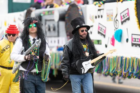 St. Louis, Missouri, USA - March 2, 2019: Bud Light Grand Parade, Men dress up as rockers throwing beads to the spectators during the parade Stock Photo - 129658615