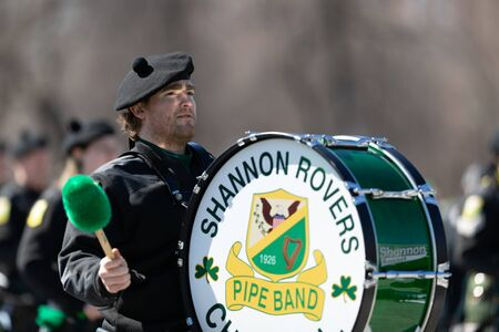 Chicago, Illinois, USA - March 16, 2019: St. Patrick's Day Parade, Members of the Shannon Rovers Pipe Band performing at the parade Фото со стока - 129744025