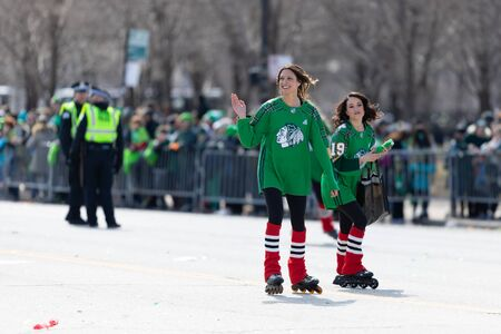 Chicago, Illinois, USA - March 16, 2019: St. Patrick's Day Parade, Woman skating on columbus drive giving away shirts during the parade
