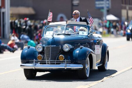 Benton Harbor, Michigan, USA - May 4, 2019: Blossomtime Festival Grand Floral Parade, Classic car carrying the parades grand marshall, retired whirpool chairman