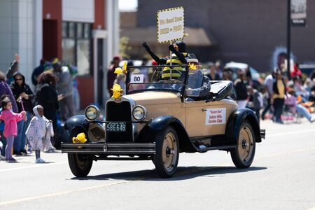 Benton Harbor, Michigan, USA - May 4, 2019: Blossomtime Festival Grand Floral Parade, classic car carrying Queen Bee from the Indian Hills garden club with a sign that says, we need bees, bees equals