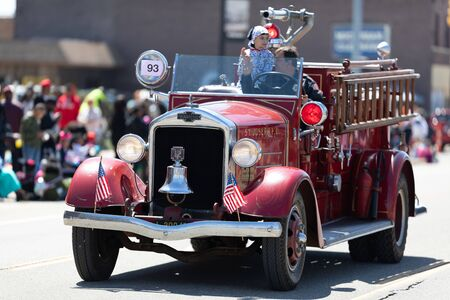 Benton Harbor, Michigan, USA - May 4, 2019: Blossomtime Festival Grand Floral Parade, Man driving an antique St Joseph firetruck during the parade Banque d'images - 130078324